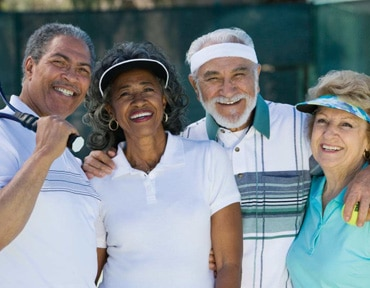 2 happy couples in 55 plus community on the tennis court